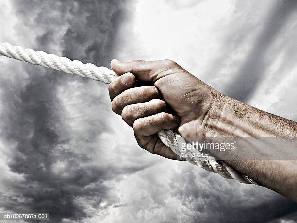 Man gripping rope, close-up of hand
