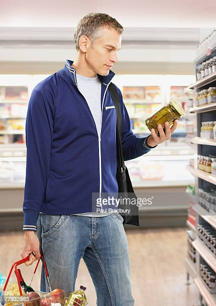 Man grocery shopping holding pickles