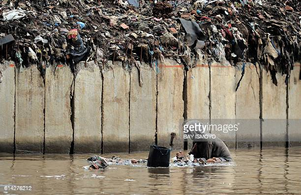 TOPSHOT A man grops the riverbed as he searches for valuable goods to resale in Jakarta on October 13 2016 Indonesia's public debt to gross domestic...