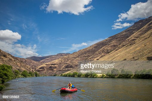 A man guides an oar raft down the Deschutes River on a sunny day.