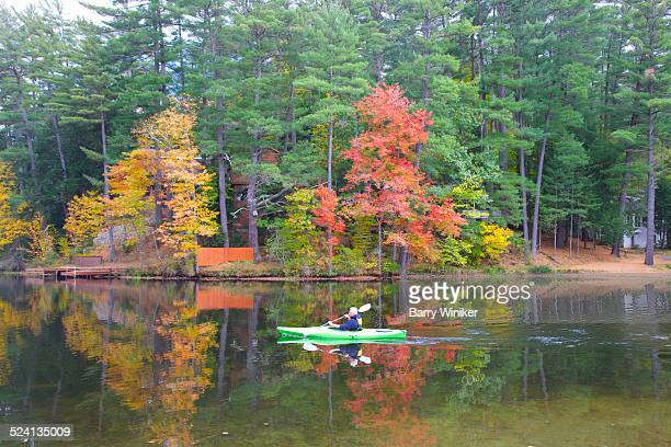 Man guiding kayak through Adirondack waters