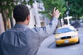 Man hailing cab in street, rear view