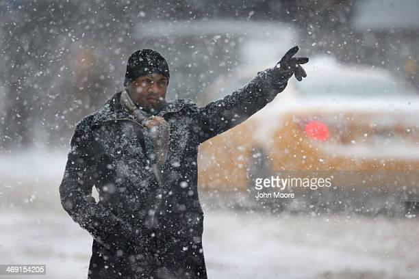 A man hails a taxi in the snow on February 13 2014 in New York City Heavy snow and high winds made for a hard morning commute in the city