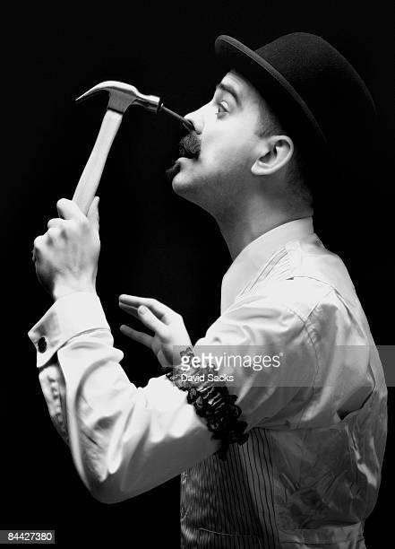 Man hammering nail into his face.