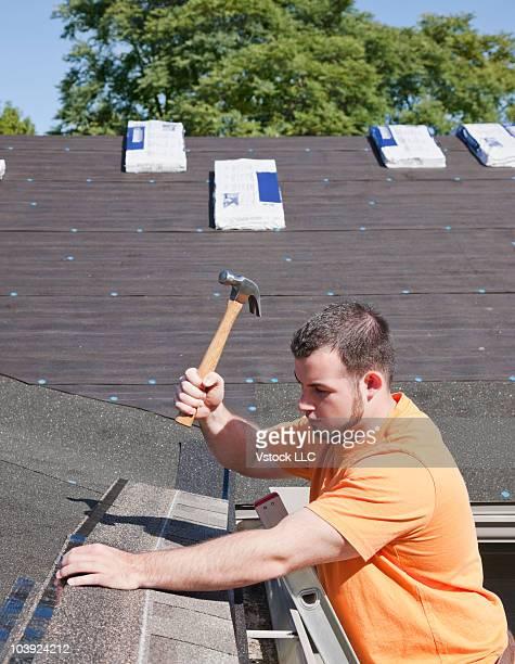 Man hammering shingles onto roof