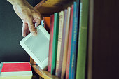 mans hand gets ebook among old paper books from the bookshelf. new technology concept