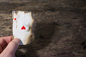 man hand holding ace of hearts abstract background playing card close up on a wood background copyspace