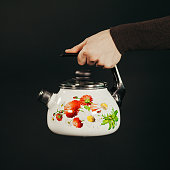 Man hand holding kettle on a black background.