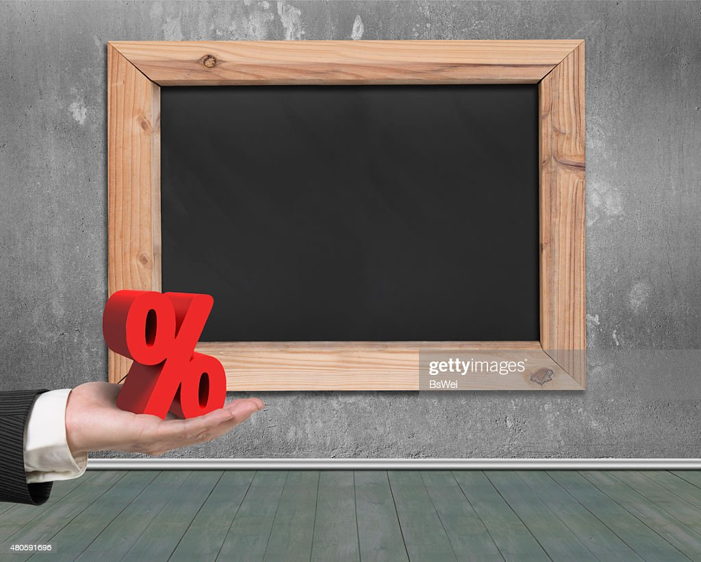 Man hand holding red percentage sign with blank blackboard : Stock Photo