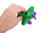Man hand holds a toy in his hand - a green children airplane with a propeller, isolated on a white background