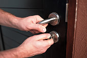 Man hand opening black door with key close up