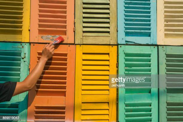 Man hand painting a muti colors decorated windows