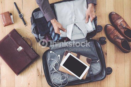 Man hand preparing business luggage : Stock Photo