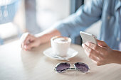 man hand texting message on social media application by phone, casual professional entrepreneur using smartphone in cafe or coffee shop, modern lifestyle and digital age concepts