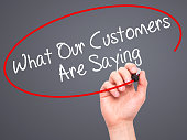 Man Hand writing What Our Customers Are Saying with black marker on visual screen. Isolated on grey. Business, technology, internet concept. Stock Photo