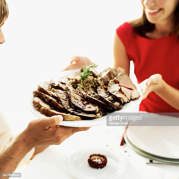 man handing a plate of roast duck to a woman at the dinner table
