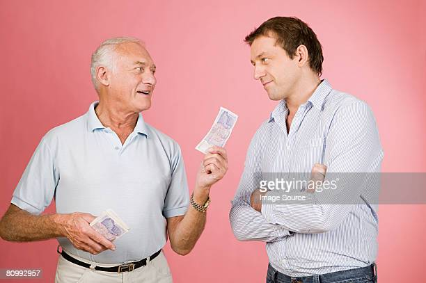 Man handing banknote to son