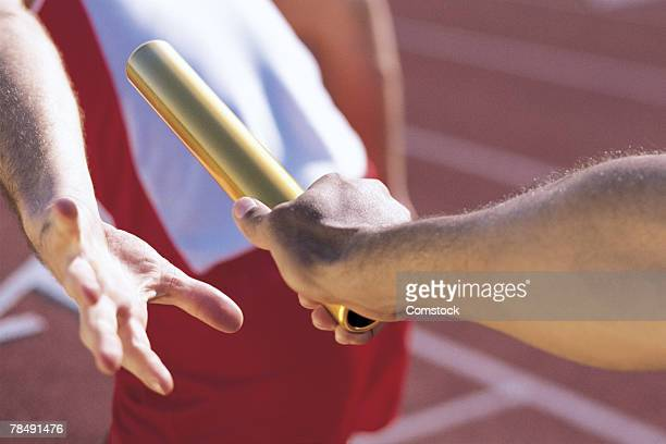 Man handing baton to another in relay race