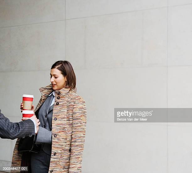 Man handing businesswoman take away coffee