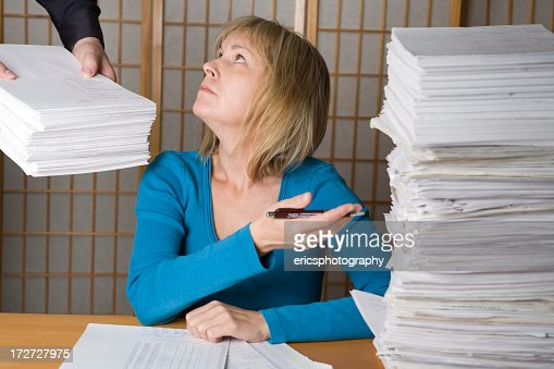 Man handing more paperwork to do to woman seated at desk