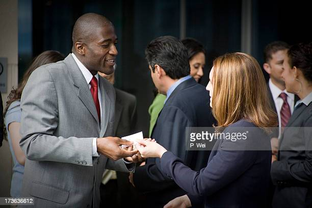 Man handing out his business card at a meet and greet
