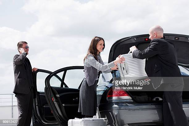 man handing suitcase to woman