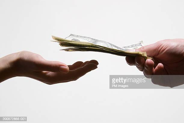 Man handing woman US dollar banknotes, close-up