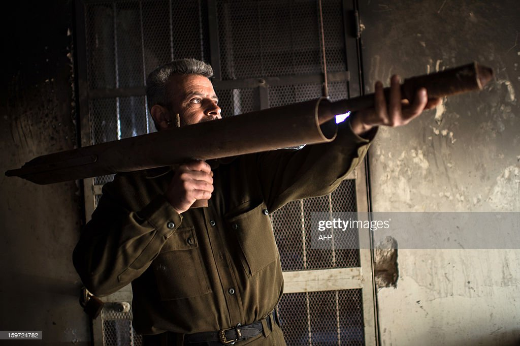 A man handles a hand made missile that he produces in a secret factory on January 19, 2013 in Al-Bab, 30 kilometers from the northeastern Syrian city of Aleppo. Recycled or non explosed bombs recolted after shellings are used for the manufacturing and sugar as well for the propulsion. Each day, nearly 50 missiles are assembled for the Abu baker Brigade.