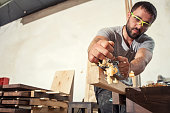 A young brunette man builder in green glasses and a gray T-shirt handles a wooden bar with a black jack plane in the workshop, in the background a lot of wooden boards