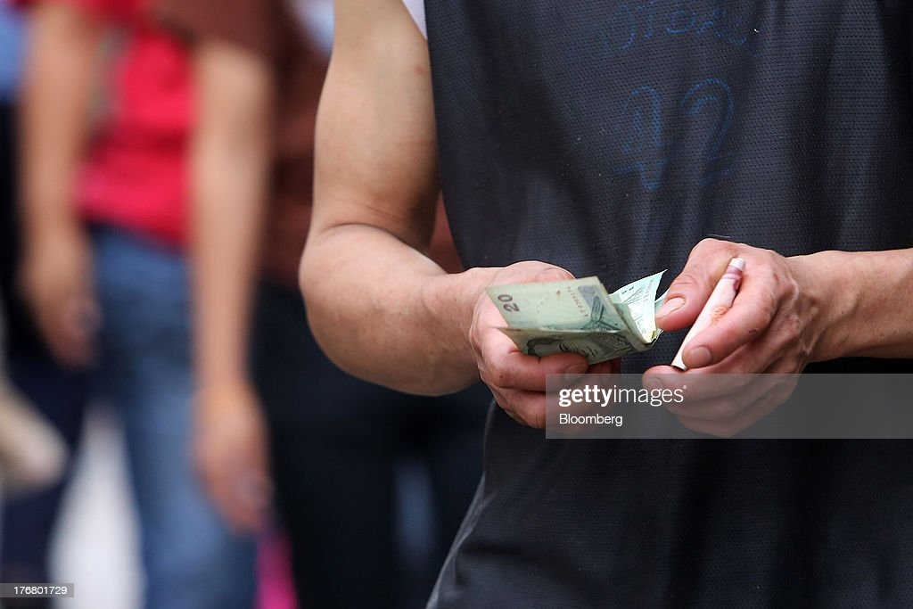 A man handles Thai baht banknotes at the Klong Thoei market in Bangkok, Thailand, on Sunday, Aug. 18, 2013. Thai economic growth slowed for a second quarter as exports cooled and local demand weakened, with rising household debt restricting the scope for monetary easing. Photographer: Dario Pignatelli/Bloomberg via Getty Images