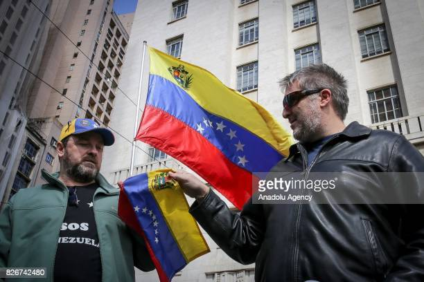 A man hands a flag of Venezuela to a protester as people gather to stage a demonstration while Foreign Ministers of Brazil Argentina Paraguay and...