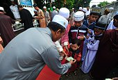 A man hands money to a child following morning prayers at a mosque on the first day of Eid alFitr celebrations in Thailand's southern province of...