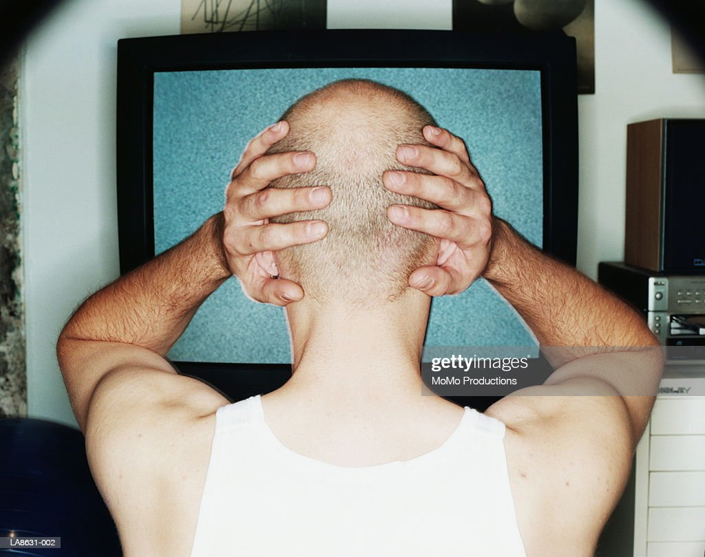 Man, hands on head, watching television, rear view : Stock Photo