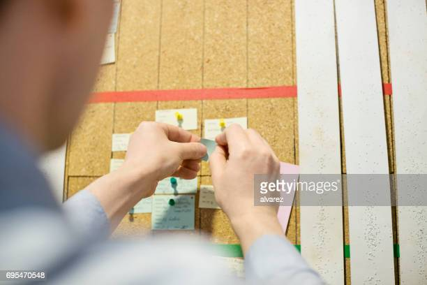 Man hands putting a paper note on cork board
