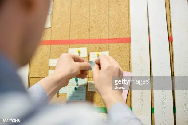 Hände des Mannes, ein Papier-Schuldbrief auf Pinnwand