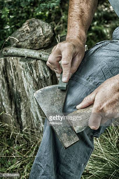 Man Hands Sharpening Rusty Old Axe with Whetstone