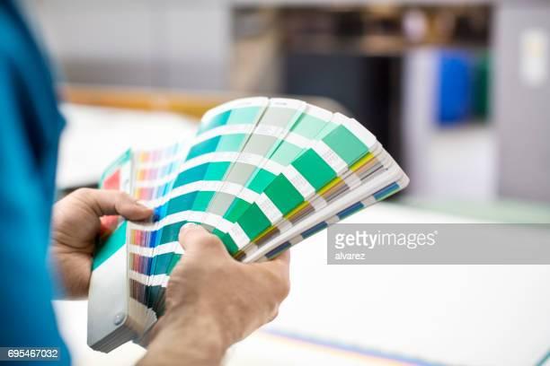 Mannhände mit Farbmuster an Druckmaschine
