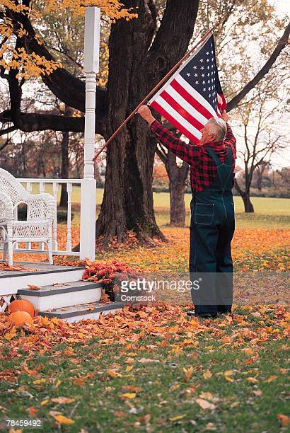 Man hanging American flag from porch