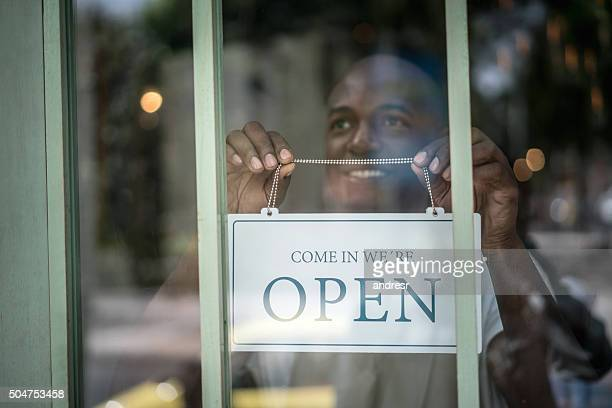 Man hanging an open sign at a restaurant