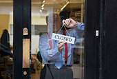 Man hanging closed sign on door