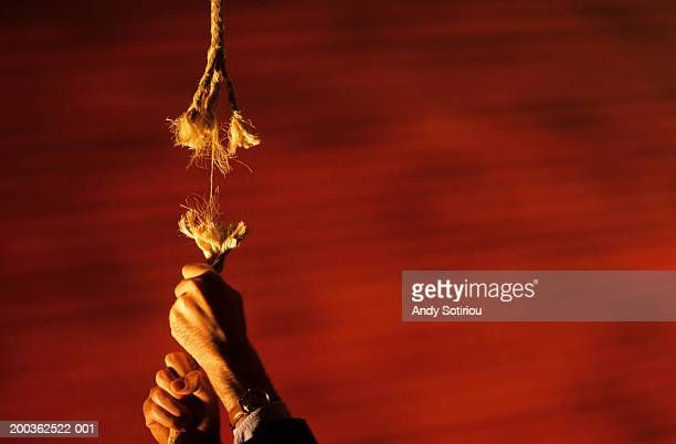 Man hanging from frayed rope, focus on hands