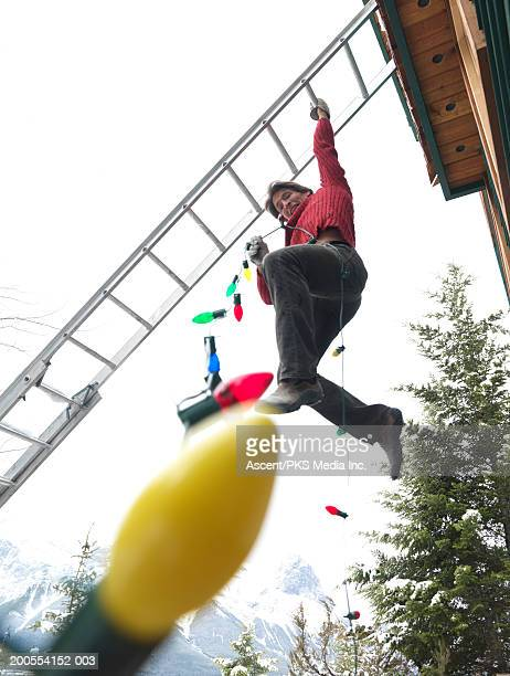 Man hanging from ladder with Christmas lights, low angle view