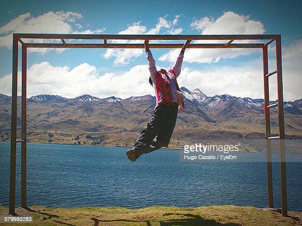 Man Hanging On Monkey Bars At Field By River Against Mountains