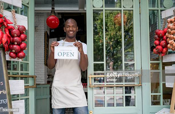Man hanging open sign at a restaurant