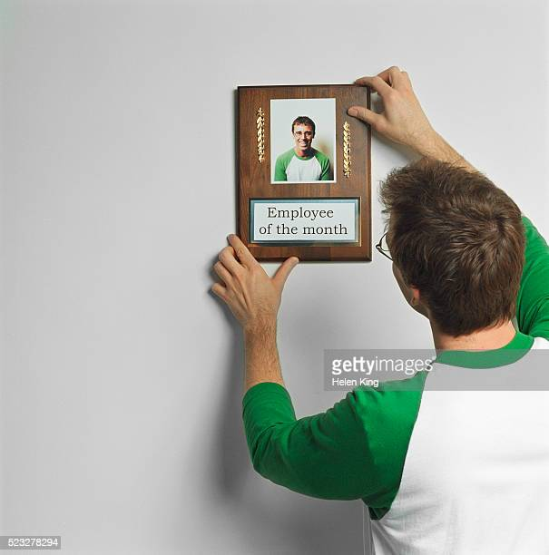 Man Hanging Picture of Himself