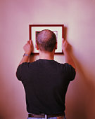 Man hanging picture on wall, rear view