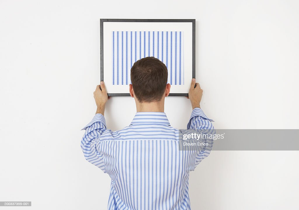 Man hanging picture on wall, rear view : Stock Photo