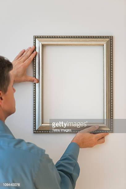 Man hanging silver frame on wall