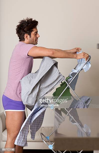 man hanging up wet clothes on dryer