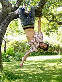 A man hanging upside down on a tree branch Stockholm Sweden.
